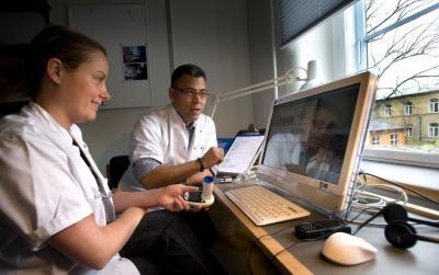 """Læge Anna Svarre Jakobsen fra Telemedicinsk Forskningsenhed på Frederiksberg Hospital sætter sig hver morgen foran skærmen for at holde stuegang med en """"udlagt"""" patient. Lungepatienten kommunikerer via en tilsvarende skærm i hjemmet. Til højre ses leder af afdelingen, Klaus Phanareth"""