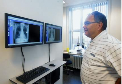 Læge Poul Dahl kigger på røntgenbilleder fra hospitalet